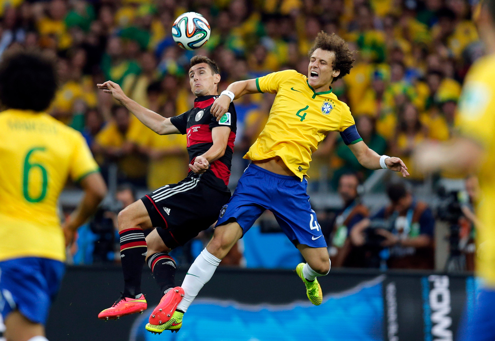 Description of . Germany's Miroslav Klose, left, and Brazil's David Luiz go for a header during the World Cup semifinal soccer match between Brazil and Germany at the Mineirao Stadium in Belo Horizonte, Brazil, Tuesday, July 8, 2014. (AP Photo/Frank Augstein)