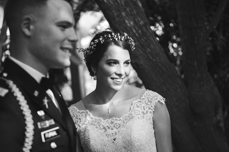 The bride illuminated by a beam of light as she smiles next to the groom.
