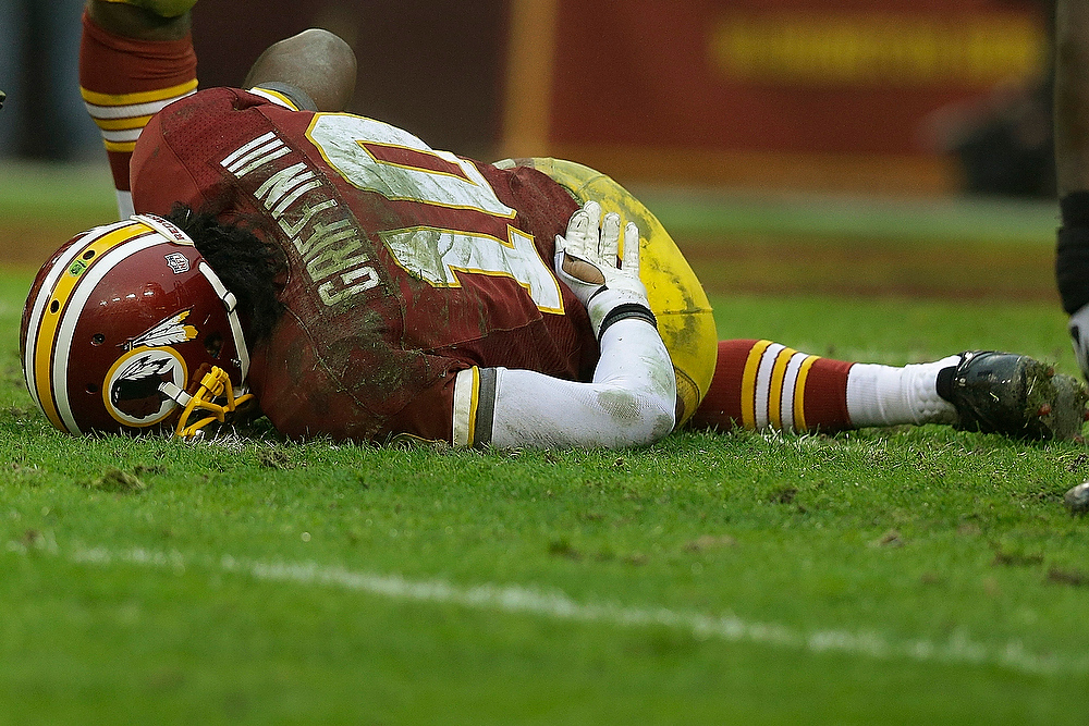 . Washington Redskins quarterback Robert Griffin III touches his back after a sack by Baltimore Ravens defensive end Arthur Jones during the second half of an NFL football game in Landover, Md., Sunday, Dec. 9, 2012. (AP Photo/Alex Brandon)