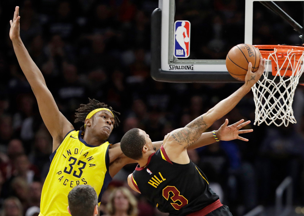 . Cleveland Cavaliers\' George Hill (3) drives to the basket and is fouled by Indiana Pacers\' Myles Turner (33) in the second half of Game 7 of an NBA basketball first-round playoff series, Sunday, April 29, 2018, in Cleveland. (AP Photo/Tony Dejak)