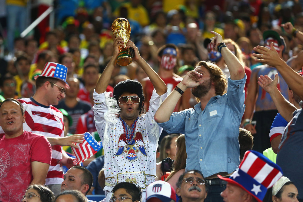 Description of . A United States fan dressed as Elvis holds up a replica of the World Cup trophy during the 2014 FIFA World Cup Brazil Group G match between Ghana and the United States at Estadio das Dunas on June 16, 2014 in Natal, Brazil.  (Photo by Michael Steele/Getty Images)