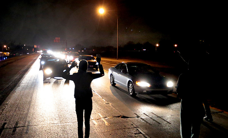 . Protesters shut down an interstate at Airport Road on Wednesday, Dec. 24, 2014, in Berkeley, Mo. Demonstrators took to the streets for a second night after a white police officer in Berkeley, Mo., killed a black 18-year-old who police said pointed a gun at him. (AP Photo/St. Louis Post-Dispatch, Robert Cohen)