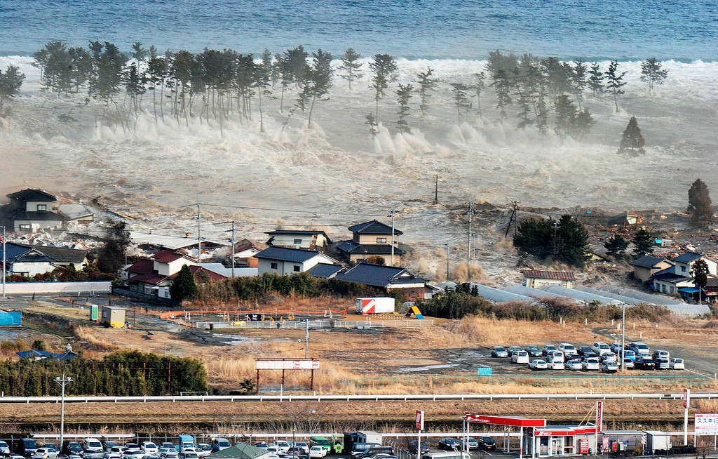 . Waves of tsunami hit residences after a powerful earthquake in Natori, Miyagi prefecture (state), Japan, Friday, March 11, 2011.  The largest earthquake in Japan\'s recorded history slammed the eastern coast Friday. (AP Photo/Kyodo News)