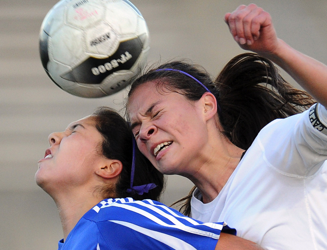 . Diamond Bar\'s Angela Schmidt, left, with the header over Bishop Amat\'s Cassandra Reyes in the first half of a CIF-SS D-3 prep soccer quarterfinal match at Diamond Bar High School on Thursday, Feb. 21, 2013 in Diamond Bar, Calif.   (Keith Birmingham/ San Gabriel Valley Tribune)