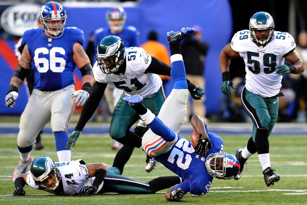 Description of . New York Giants running back David Wilson (22) dives for a first down as he is tackled by Philadelphia Eagles' Jamar Chaney (51) and Nnamdi Asomugha (24) during the second half of an NFL football game, Sunday, Dec. 30, 2012 in East Rutherford, N.J. The Giants won 42-7. (AP Photo/Bill Kostroun)