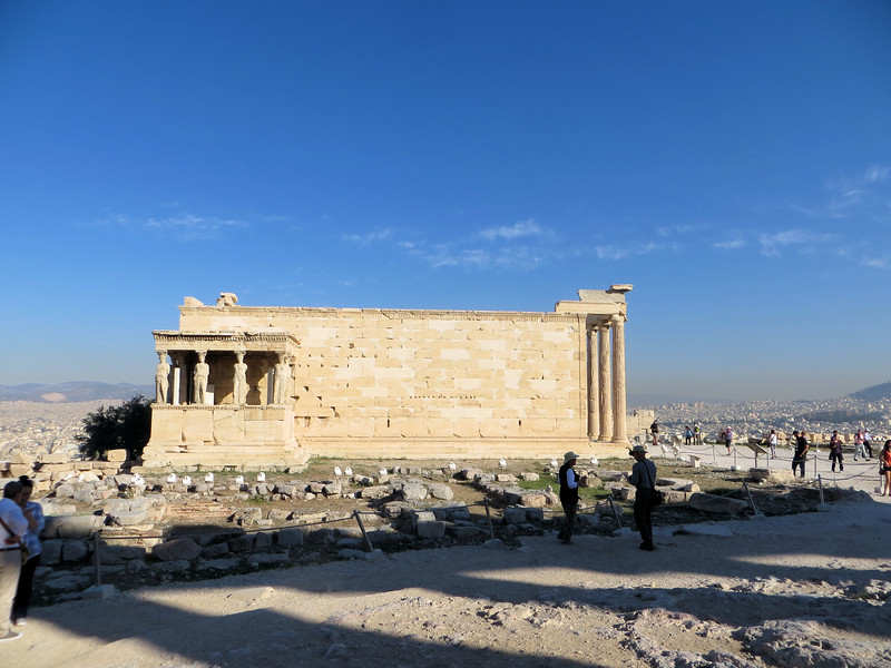 """The design is not that of a """"typical"""" Greek temple.  It is not flat, but is built on two levels, due to its position on the side of a hill.  If you stand beside the north wall of the Parthenon this is the view of the Erechtheion you would see.  The temple housed the cults of two gods:  Athena and Poseidon, plus it was believed to contain the graves of two mythical kings, Erechtehos and Kekrops.  This was also considered by Athenians to be the spot where Athena and Poseidon had a fight over who was going to be the patron of Athens.  Each offered the Athenians a gift.  Athena offered the olive tree, representative of the area's agricultural wealth, and Poseidon offered the sea, with its strategic position along the Aegean trade routes.  The Athenians, obviously, picked Athena and so the contest was decided."""