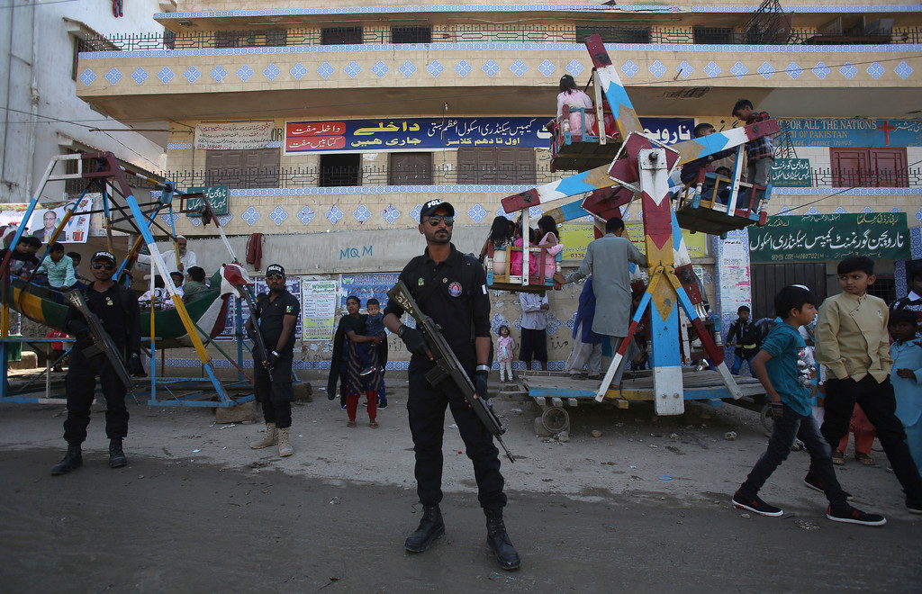 . Pakistani police cammondos stand guard while Christians children enjoy ride to celebrate Christmas in Karachi, Pakistan, Monday, Dec. 25, 2017. (AP Photo/Fareed Khan)