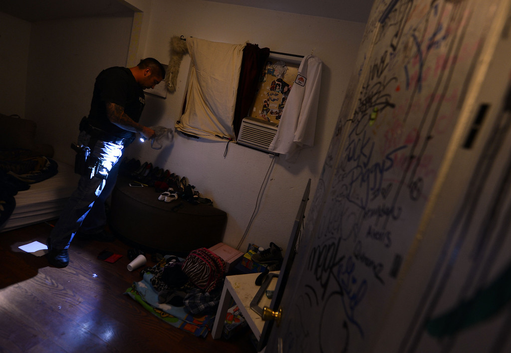. (Will Lester/Inland Valley Daily Bulletin) A law enforcement officer checks a room for drugs inside a home known to house gang members who are on probation Saturday night. The Pomona Police Department, along with assistance from other law enforcement agencies, conducted a Gang Saturation Sweep Saturday August 17, 2013.