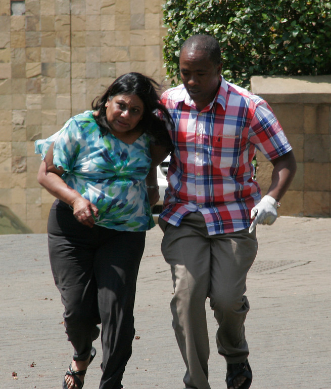 . A security official escorts a woman outside the Westgate Mall in Nairobi, Kenya Saturday Sept. 21, 2013, where shooting erupted when armed men attempted to rob a shop, according to police. Witnesses say a half dozen grenades also went off along with volleys of gunfire in and around the mall. (AP Photo/Sayyid Azim)