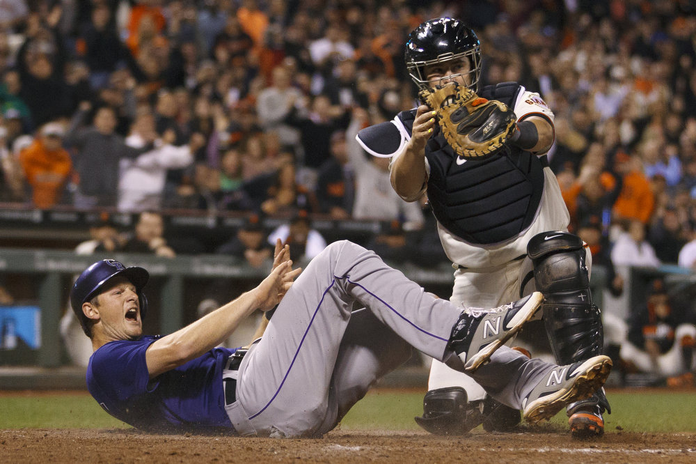 . DJ LeMahieu #9 of the Colorado Rockies is tagged out by Andrew Susac #34 of the San Francisco Giants at home plate during the seventh inning at AT&T Park on August 25, 2014 in San Francisco, California.  (Photo by Jason O. Watson/Getty Images)