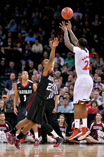 March 20, 2014: Cincinnati Bearcats guard Sean Kilpatrick (23) shoots over Harvard Crimson guard/forward Wesley Saunders (23) during a second round game of the NCAA Division I Men's Basketball Championship between the 5-seed Cincinnati Bearcats and the 12-seed Harvard Crimson at Spokane Arena in Spokane, Wash. Harvard defeated Cincinnati 61-57.