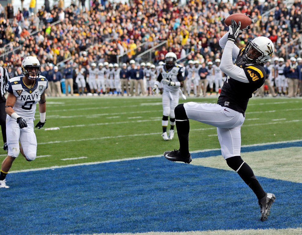 . Arizona State wide receiver Alonzo Agwuenu, right, catches an 11-yard touchdown pass near Navy safety Wave Ryder (8) during the first half of the Fight Hunger Bowl NCAA college football game in San Francisco, Saturday, Dec. 29, 2012. (AP Photo/Marcio Jose Sanchez)