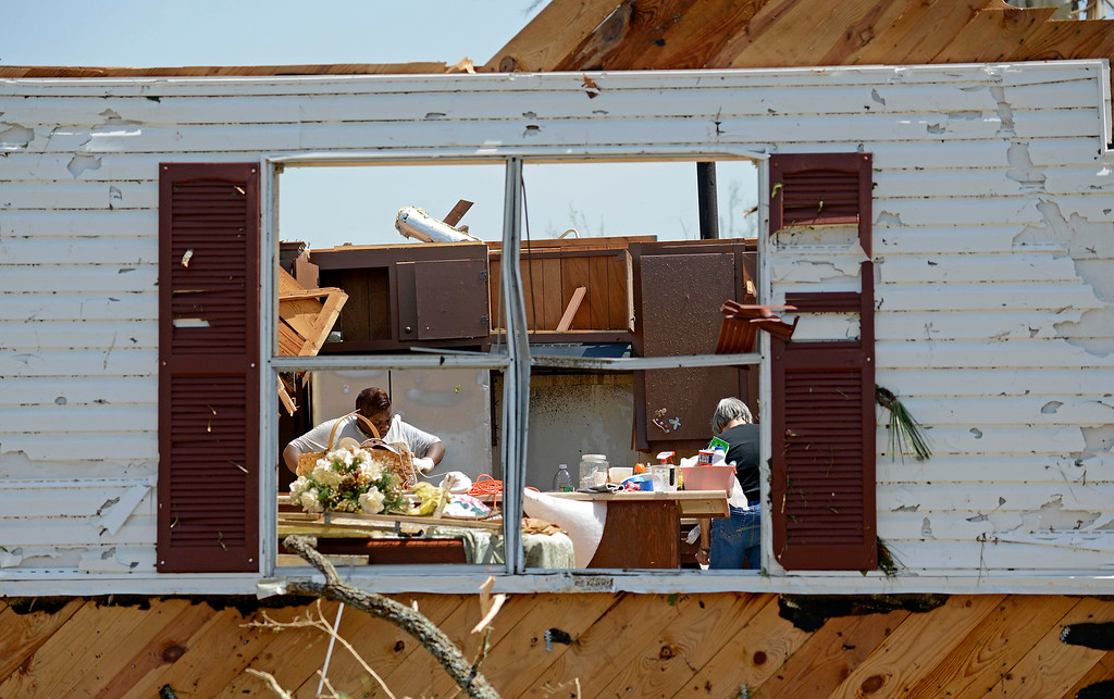 . Bobbi Leggon and Sudie Carter work to salvage items from a friend\'s home on Clayton Avenue in Tupelo, Miss., Tuesday, April 29, 2014.  (AP Photo/Thomas Graning)
