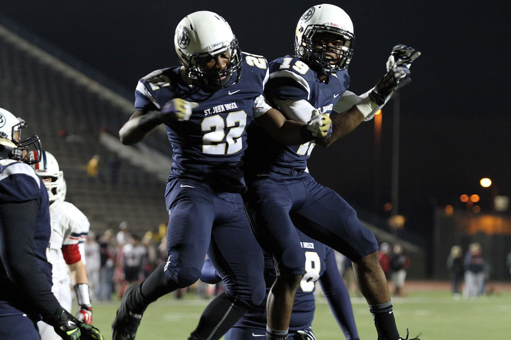 . November 22, 2013-Photo by Tracey Roman/for the Press-Telegram  St. John Boscos Clifford Simms  and Anselem Umeh celebrate Simms touchdown in the third quarter putting the Braves at 55-0 over Tesoro.