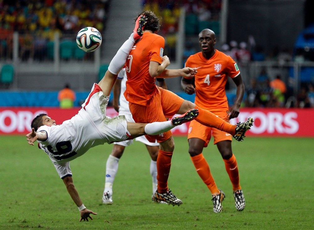 . Costa Rica\'s Cristian Gamboa clears the ball with a scissor kick next to Netherlands\' Daley Blind during the World Cup quarterfinal soccer match at the Arena Fonte Nova in Salvador, Brazil, Saturday, July 5, 2014. (AP Photo/Natacha Pisarenko)