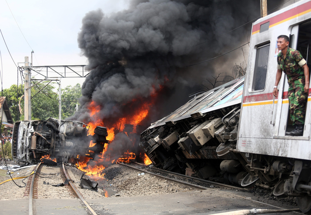 . An Indonesian soldier looks out from a collided commuter train in Jakarta, Indonesia, 09 December 2013. A commuter train ploughed into a truck carrying petrol in the Indonesian capital Jakarta, killing at least seven people and injuring more than 60, police said. The crash at a level crossing in south Jakarta sparked an explosion and sent a column of fire into the sky, television footage showed.  EPA/HERIYAWAN
