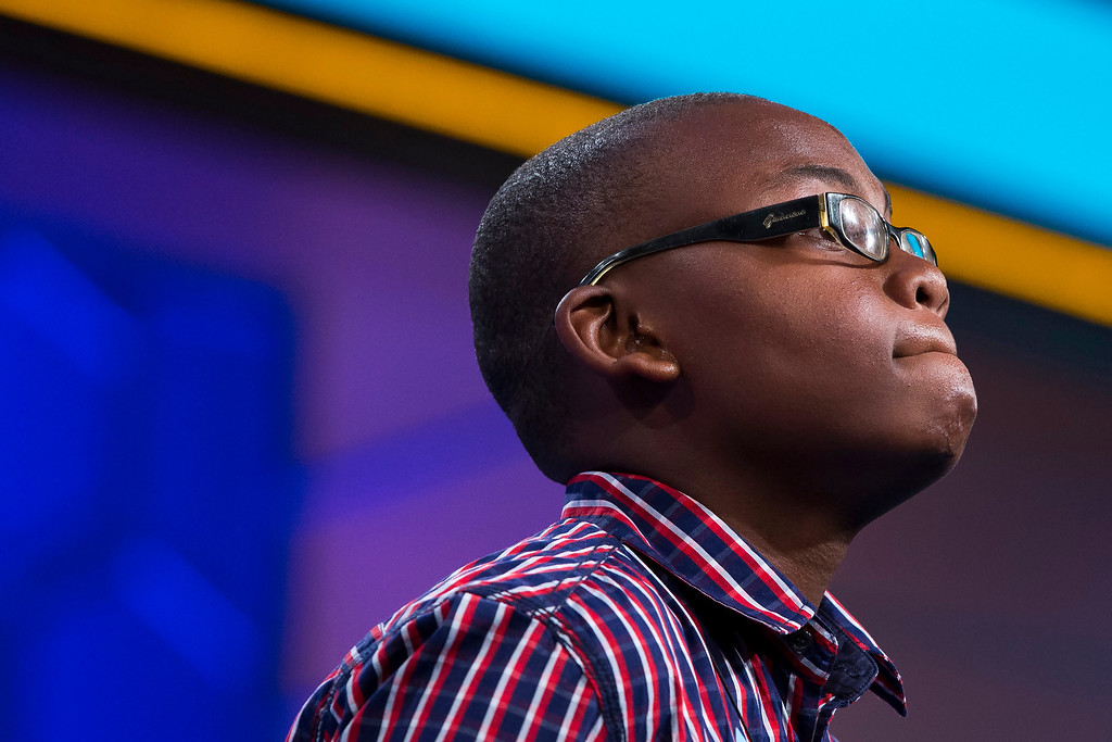 ". Tajaun Gibbison of Mandeville, Jamaica, pauses while spelling the word ""swidden\"" correctly during the semifinal round of the National Spelling Bee, on Thursday, May 29, 2014, in Oxon Hill, Md. (AP Photo/ Evan Vucci)"