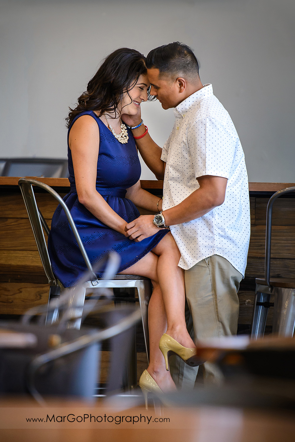 romantic shot of woman in blue dress and man in white shirt looking at each other during engagement session at San Pedro Square Market in San Jose