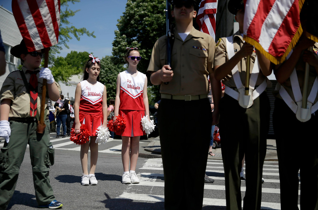 . Participants stand at attention during the opening ceremonies before a Memorial Day parade in the Glenwood neighborhood of New York, Monday, May 25, 2015. President Barack Obama saluted Americans who died in battle Monday, noting the first Memorial Day in 14 years without U.S. forces involved in a major ground war. (AP Photo/Seth Wenig)