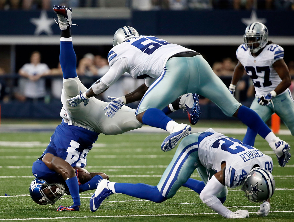. New York Giants tight end Larry Donnell (84) is upended after catching a pass by Dallas Cowboys middle linebacker Rolando McClain (55) and free safety Barry Church (42) during the first half of an NFL football game Sunday, Oct. 19, 2014, in Arlington, Texas. (AP Photo/Brandon Wade)