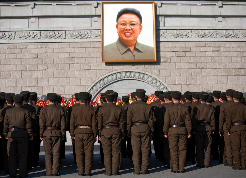 Description of . North Korean soldiers gather to lay flowers on a stage in front of a large portrait of the late Kim Jong Il as they pay their respects on the first day of the Lunar New Year holiday at Kim Il Sung Square in Pyongyang on Monday, Jan. 23, 2012. Pyongyang residents said they were encouraged to celebrate the traditional holiday as they usually do, despite the death of Kim Jong Il, only the second leader North Koreans have known since the nation was founded in 1948.  (AP Photo/David Guttenfelder)