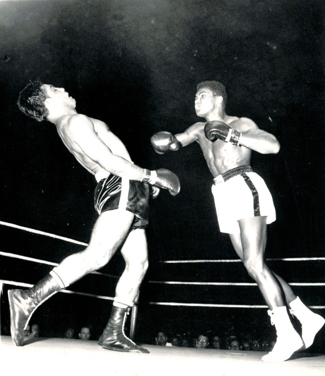 . Rock \'n\' Roll in the Ring   Alex Miteff stiffens shortly before hitting the canvas under furious attack by Cassius Clay.  The Argentinian signaled the referee he was unable to continue their nationally televised Louisville, Ky., fight and Clay was awarded a sixth-round technical knockout. 1961  Credit: AP