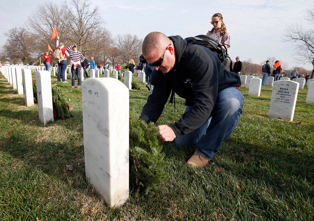 . Randy Schultz, from Union Bridge, Md., places a wreath at a grave as part of Wreaths Across America at Arlington National Cemetery, Saturday, Dec. 12, 2015 in Arlington, Va. Organizers estimated that volunteers placed 240,815 wreaths at Arlington. (AP Photo/Alex Brandon)