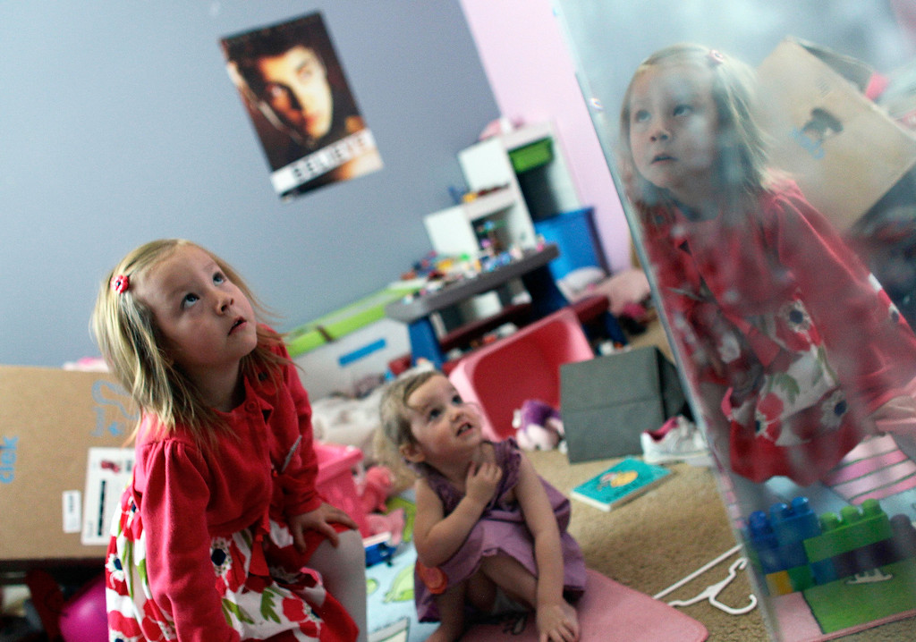 . In this Monday, Feb. 25, 2013, photo, Coy Mathis, left, plays with her sister, Auri, 2, center, near a mirror at their home in Fountain, Colo.  (AP Photo/Brennan Linsley)