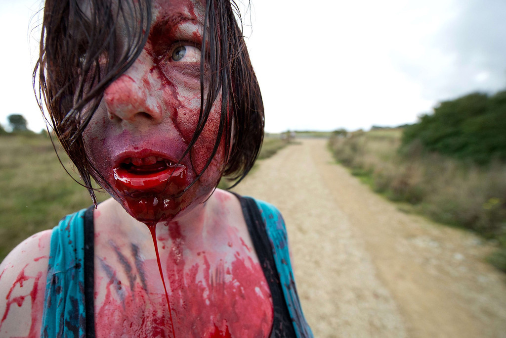 """. A volunteer \""""zombie\"""" waits for participants during one of Britain\'s biggest horror events, the \""""Zombie Evacuation Race\"""" at Carver Barracks near Saffron Walden, England, on October 5, 2013. The race sees thousands of participants attempt to complete a gruelling 5 kilometre cross-country run, while evading \""""zombies\"""", intent on snatching the three life-line strips hanging from every runner\'s waist.  Those who manage to get through with any strips remaining are named as survivors while those without take home an \""""infected\"""" badge.  LEON NEAL/AFP/Getty Images"""