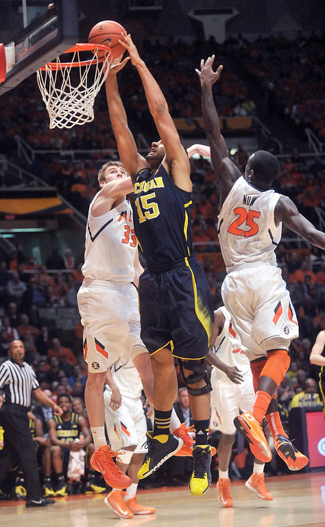 . Michigan forward Jon Horford (15) goes up for a dunk between Illinois forward Jon Ekey (33) and guard Kendrick Nunn (25) during the second half of an NCAA college basketball game Tuesday, March 4, 2014, in Champaign, Ill. Michigan won 84-53. (AP Photo/Rick Danzl)