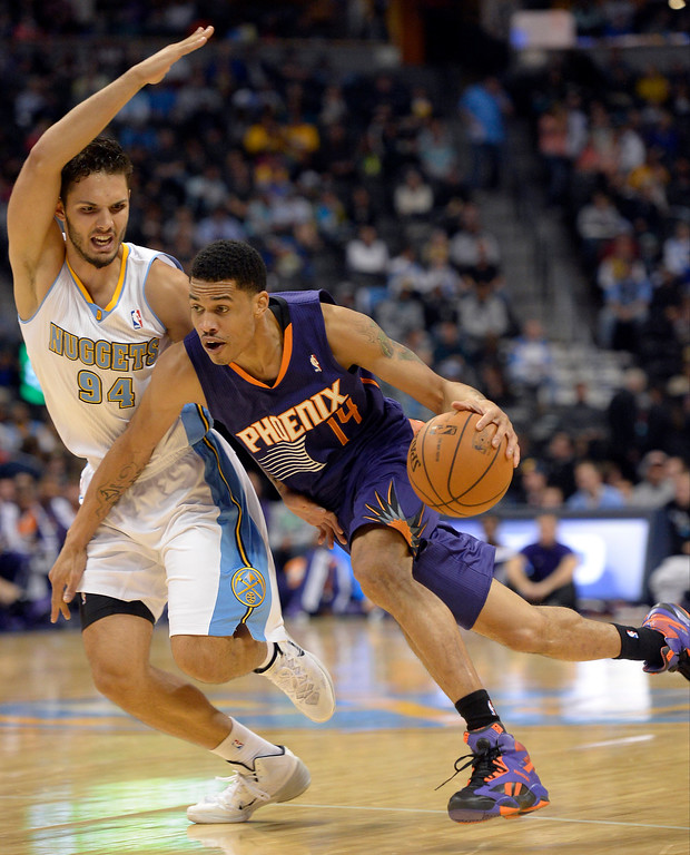 . Denver Nuggets shooting guard Evan Fournier (94) draws the foul on Phoenix Suns shooting guard Gerald Green (14) during the third quarter October 23, 2013 at Pepsi Center. (Photo By John Leyba/The Denver Post)