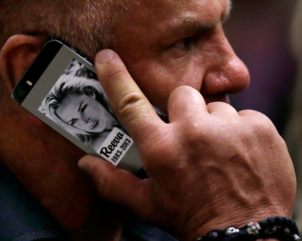 . Former football player Mark Batchelor speaks on his mobile phone, bearing a photo of the late Reeva Steenkamp, as he sits in court after Oscar Pistorius\' sentencing in Pretoria, South Africa, Tuesday, Oct. 21, 2014. (AP Photo/Themba Hadebe, Pool)