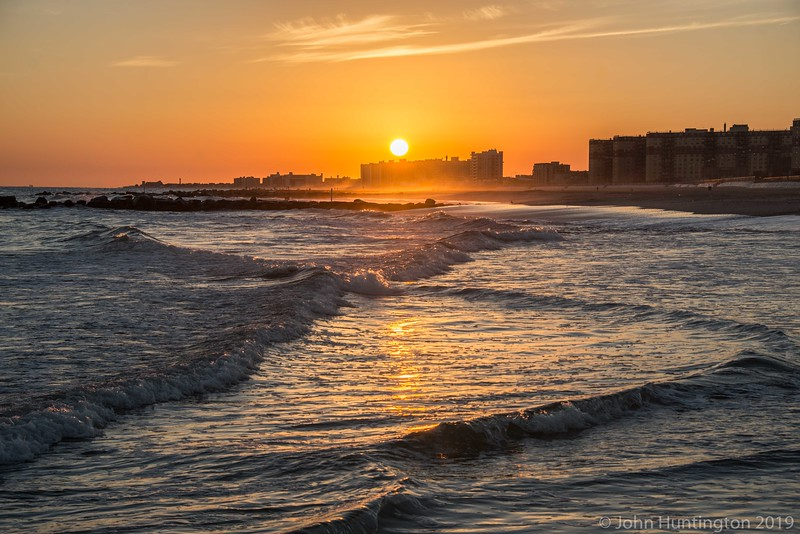 Sunset over breaking waves in the Rockaways, Queens, New York City.