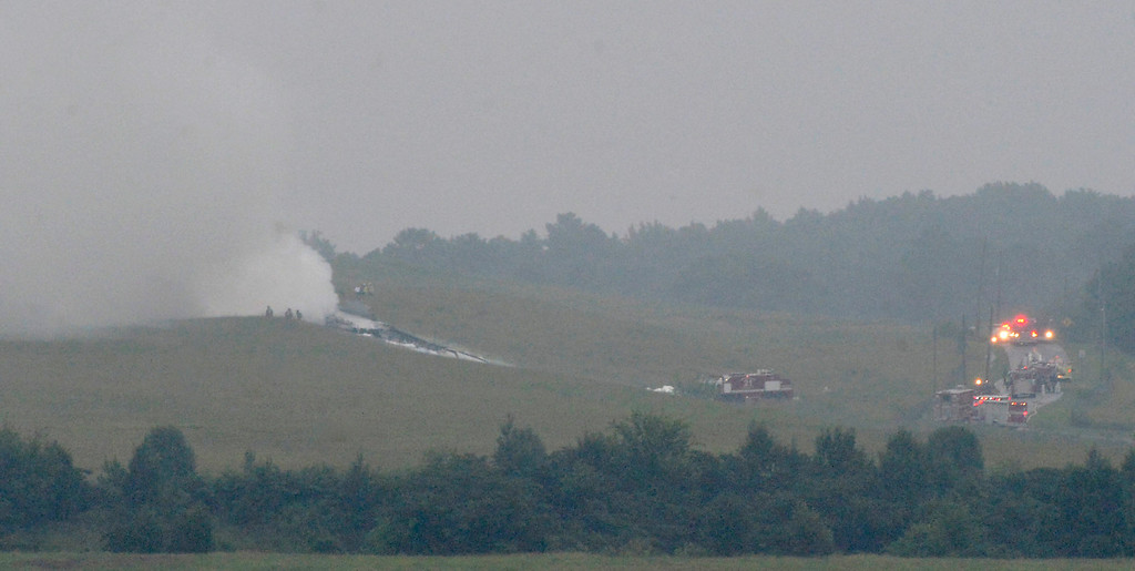 . A UPS cargo plane lies on a hill at Birmingham-Shuttlesworth International Airport after crashing on approach, Wednesday, Aug. 14,  2013, in Birmingham, Ala.  (AP Photo/ AL.com, Mark Almond)