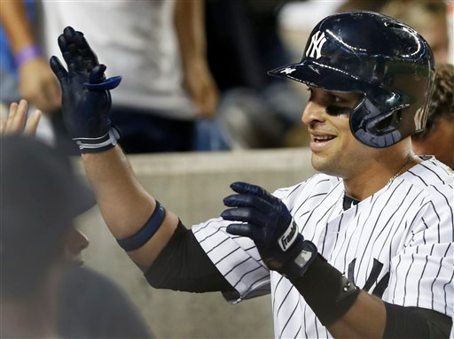 . New York Yankees Martin Prado celebrates with teammates in the dugout after hitting a fifth-inning, solo home run in the Yankees 4-3 loss to the Detroit Tigers in a baseball game at Yankee Stadium in New York, Tuesday, Aug. 5, 2014.  (AP Photo/Kathy Willens)
