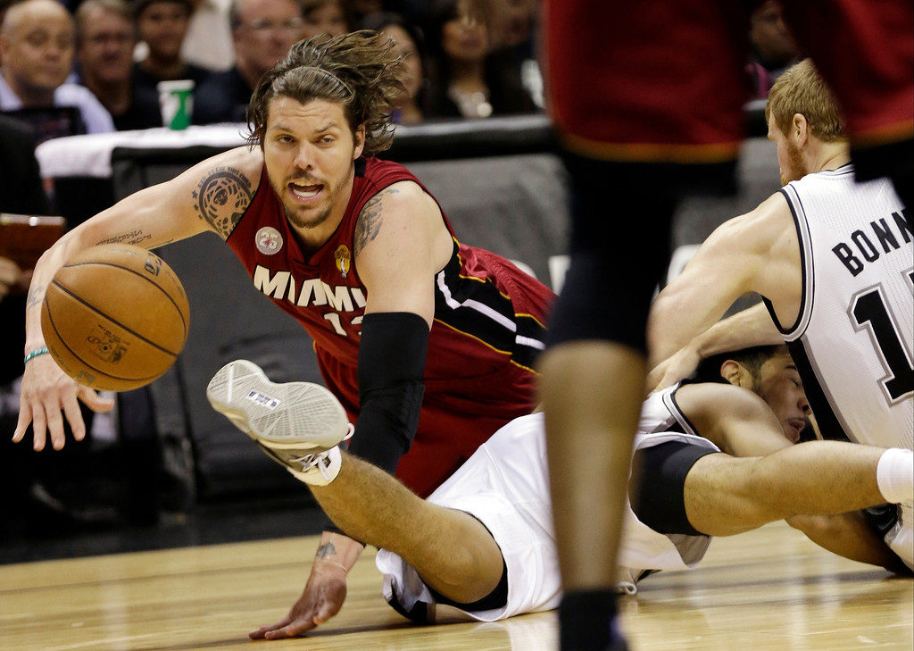 . Miami Heat shooting guard Mike Miller, San Antonio Spurs point guard Cory Joseph and Matt Bonner, right, battle for a loose ball during the first half at Game 3 of the NBA Finals basketball series, Tuesday, June 11, 2013, in San Antonio. (AP Photo/Eric Gay)
