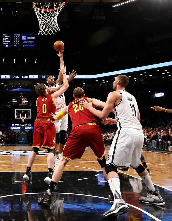 . Brooklyn Nets forward Thaddeus Young (30) shoots over Cleveland Cavaliers forward Kevin Love (0) with Cavaliers center Timofey Mozgov (20) defending Nets center Brook Lopez (11) in the first half of an NBA basketball game, Wednesday, Jan. 20, 2016, in New York. The Cavaliers defeated the Nets 91-78. (AP Photo/Kathy Willens)