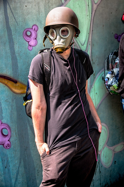 """A counterprotester wearing a gas mask stands relaxed on the sidewalk opposite the """"Liberty or Death"""" rally."""