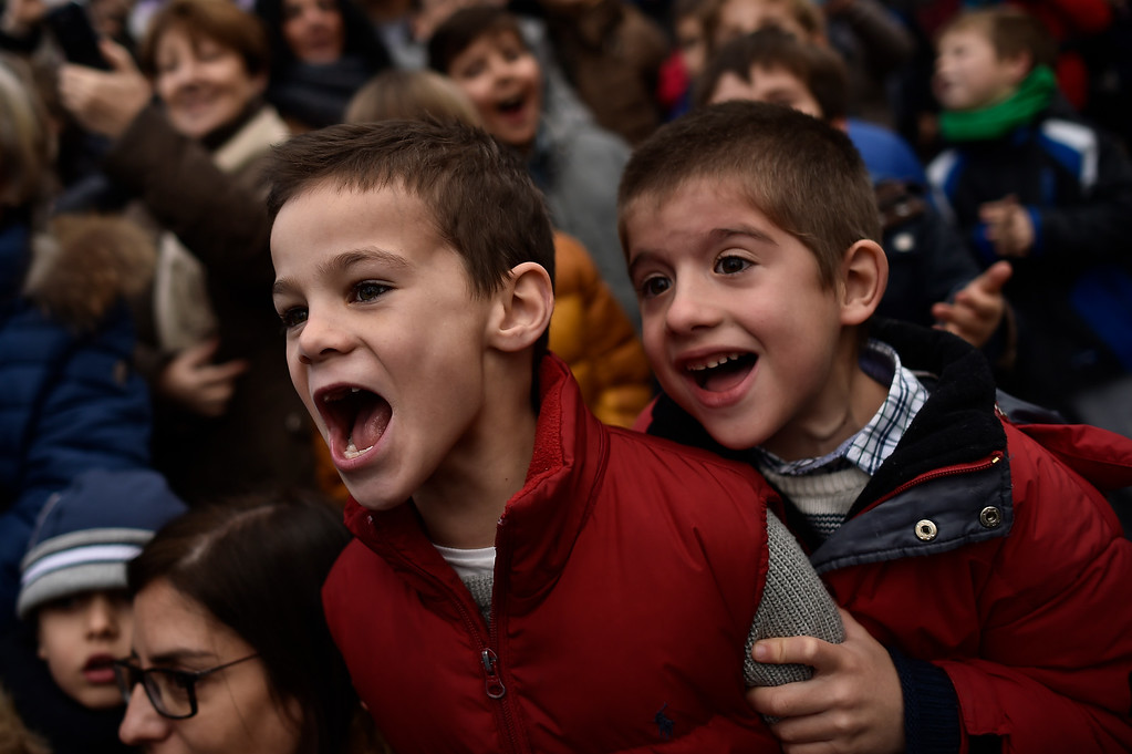 . Two boys enjoy the Cabalgata Los Reyes Magos (Cavalcade of the three kings) the day before Epiphany, in Pamplona, northern Spain, Tuesday, Jan. 5, 2016. It is a parade symbolizing the coming of the Magi to Bethlehem following the birth of Jesus. In Spain and many Latin American countries Epiphany is the day when gifts are exchanged. (AP Photo/Alvaro Barrientos)