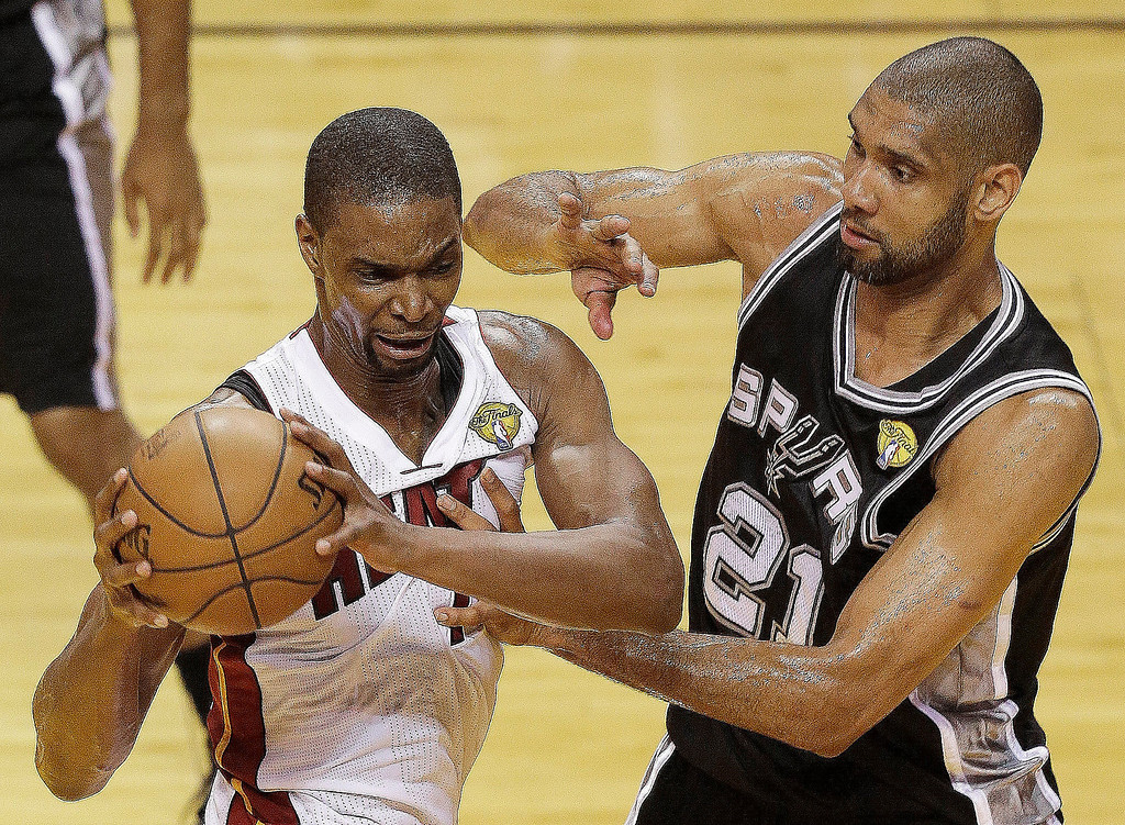 . Miami Heat center Chris Bosh (1) and San Antonio Spurs power forward Tim Duncan (21) work during the second half of Game 2 of the NBA Finals basketball game, Sunday, June 9, 2013 in Miami.  (AP Photo/Wilfredo Lee)