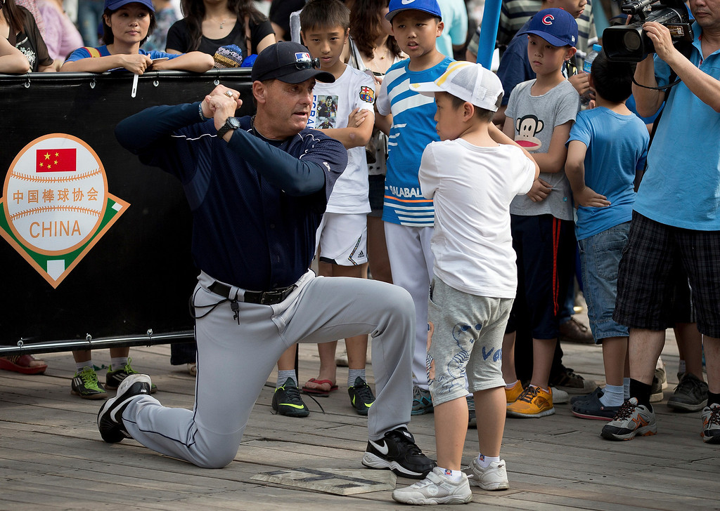. Rick Dell, director of Baseball Development in Asia for Major League Baseball (MLB), left, teaches a Chinese boy how to bat during an event held at a shopping mall, on International Children\'s Day in Beijing Saturday, June 1, 2013. (AP Photo/Andy Wong)