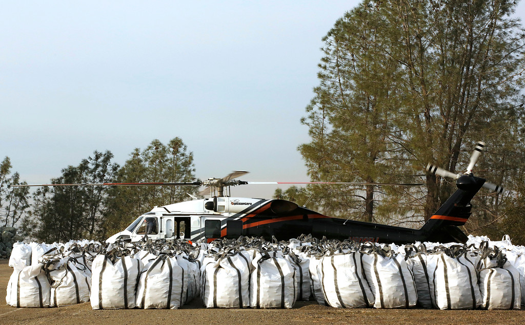 . A helicopter sits at a staging area behind bags of rocks near the Oroville Dam, Monday, Feb. 13, 2017, in Oroville, Calif. Officials from the California Department of Water Resources were considering using helicopters to drop loads of rock on the eroded spillway at Lake Oroville. (AP Photo/Rich Pedroncelli)