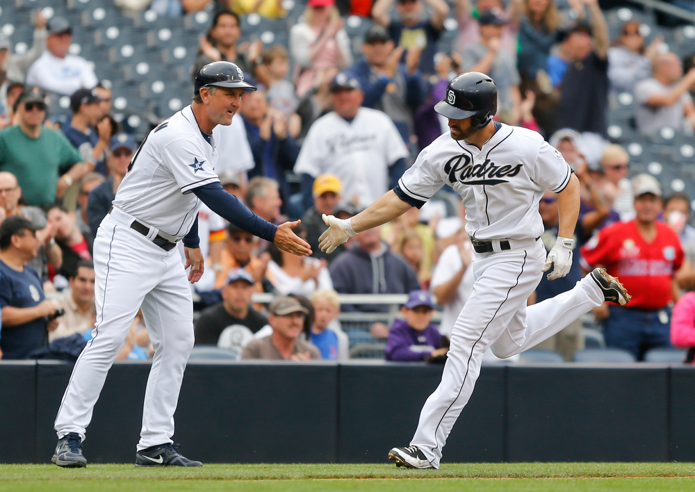 . San Diego Padres\' Xavier Nady is congratulated by third base coach Glenn Hoffman while rounding the bases on a solo home run against the Colorado Rockies during the fourth inning of a baseball game Thursday, April 17, 2014, in San Diego.  (AP Photo/Lenny Ignelzi)
