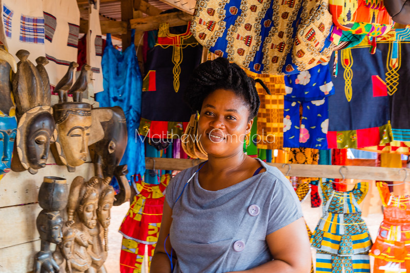 Smiling Ivorian lady vendor in a roadside kiosk selling African Arts, crafts, clothes, bags, and gift materials  in Yamoussoukro Ivory Coast, Cote d'Ivoire. She has a beautiful African hair style, braiding, Nice complexion.