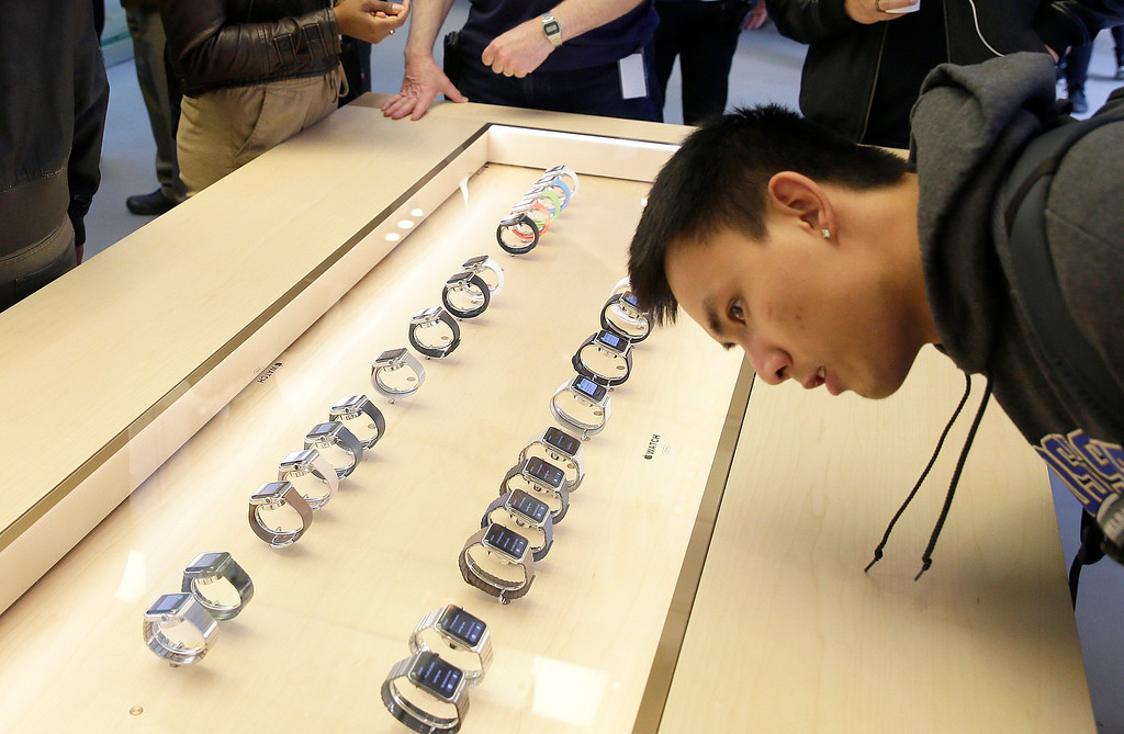 . A customer looks at a line of Apple\'s new watches displayed at a store in San Francisco, Friday, April 10, 2015. Apple has started taking orders for the watch on its website and the Apple Store app. Currently, that\'s the only way Apple is selling the watch, with shipments scheduled to start April 24. (AP Photo/Eric Risberg)
