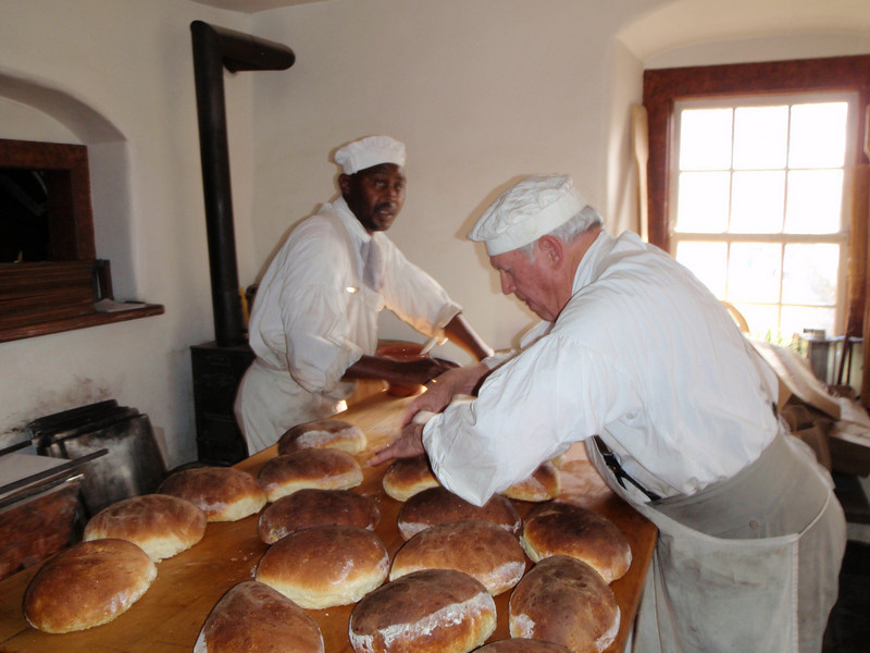 Old Salem bakers with fresh bread loaves out of the oven