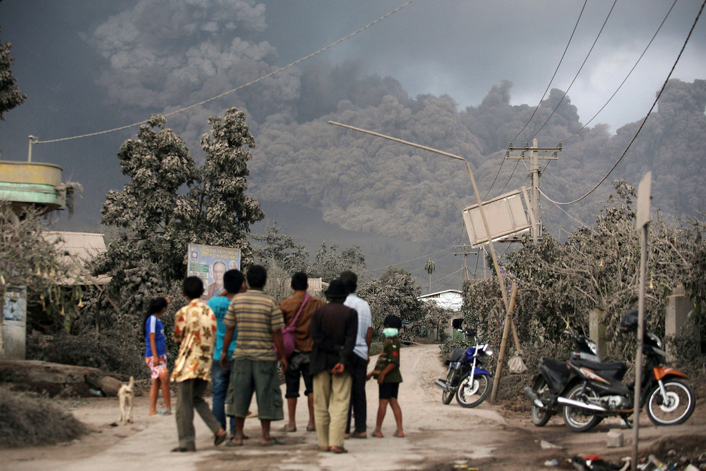 . Villagers watch as Mount Sinabung releases pyroclastic flow in Sibintun, North Sumatra, Indonesia, Monday, Jan. 6, 2014. The volcano unleashed more clouds of searing gas avalanching down the mountain with a thunderous roar, forcing tens of thousands of people packed emergency shelters. (AP Photo/Binsar Bakkara)