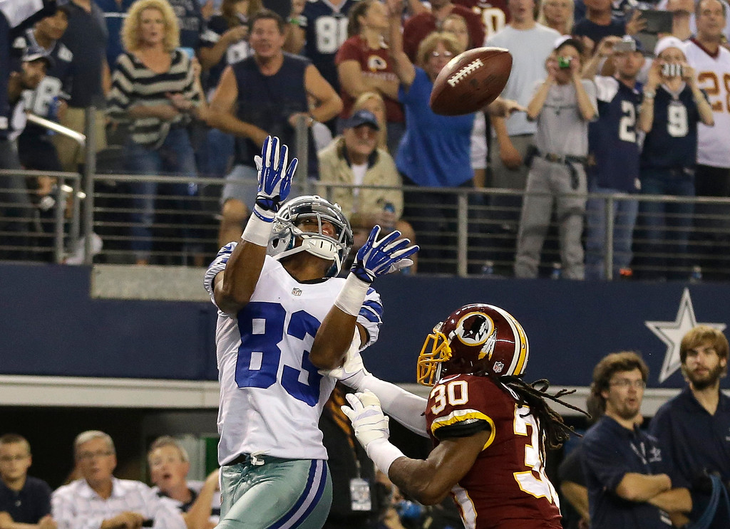 . Fans look on as Dallas Cowboys wide receiver Terrance Williams (83) goes up for a touchdown grab as Washington Redskins cornerback E.J. Biggers (30) defends in the second half of an NFL football game, Sunday, Oct. 13, 2013, in Arlington, Texas. (AP Photo/LM Otero)