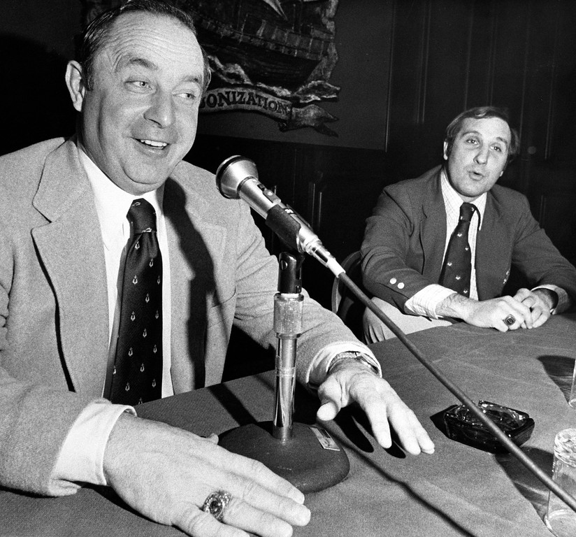 . Earle Bruce, left, in his fifth season as Iowa State University football coach and Bo Rein, in his second season with North Carolina State, speak to reporters at a hotel in Atanta, Ga., Dec. 30, 1977. Their teams are in Atlanta for the Peach Bowl. (AP Photo/Steve Helber)