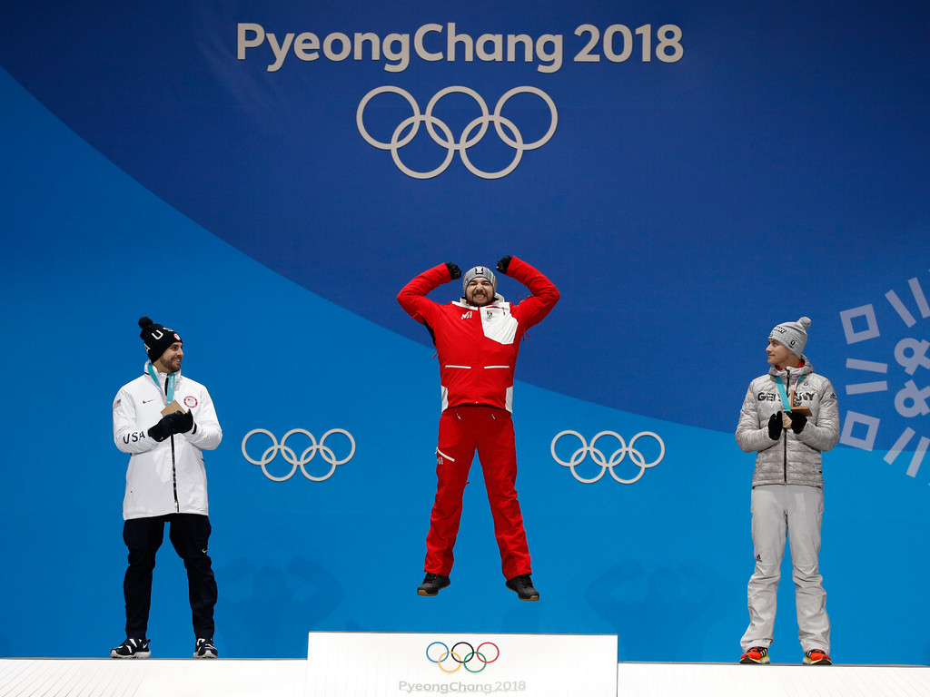 . Men\'s luge silver medalist Chris Mazdzer, left, of United States, and bronze medalist Johannes Ludwig, right, of Germany, applaud as gold medalist David Gleirscher, right, of Austria, celebrates during their medals ceremony at the 2018 Winter Olympics in Pyeongchang, South Korea, Monday, Feb. 12, 2018. (AP Photo/Jae C. Hong)